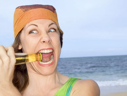 10 Everyday Habits That Ruin Your Oral Health_woman biting bottle cap